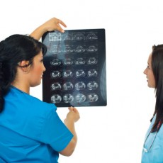 Two radiologists woman  holding a magnetic resonance imaging and comments  and discuss together isolated on white background