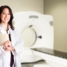 Beautiful happy female doctor physician radiologist holding patient medical chart and pen standing in CT CAT Scan room at hospital, isolated.