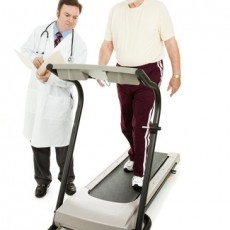 Doctor monitoring a senior man as he walks on a treadmill.  Full body isolated on white.